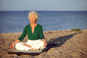 bigstock-Elderly-Woman-On-Beach-Meditat-52950844